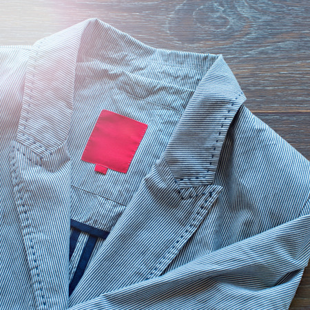 Lightweight striped cotton jacket with a fashionable brooch on wooden background. The concept of fashion and design