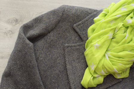 Womens coat gray color and scarf yellow. Textured background, the concept of fashion and design Stock Photo