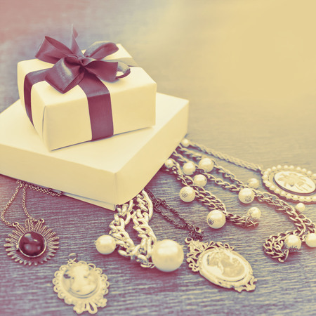 Decorative composition vintage style gift box set decoration ribbon satin bow women's jewelry necklace comeo pearls wooden background. Retro toning light effect