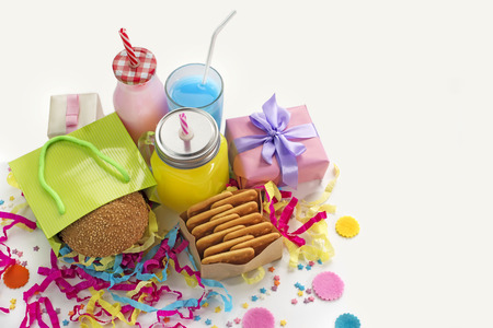 Festive composition of drinks, snacks, holiday hamburger, cookie, tinsel, confetti, gift box, cocktail and saturated colors. Children's holiday birthday party