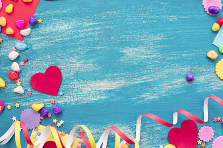 Festive confetti background heart candy color saturated. Wood old blue background with copy space flat lay