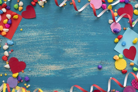Decorative holiday background with streamers confetti candy hearts decor. Blue shabby wooden top view background flat lay Stockfoto