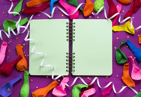 Uncovered notebook for records on a purple festive background colored balloons streamers Top view festive background copy space