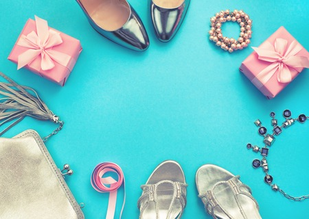 Set of fashion accessories flat lay shoes handbag necklace jewelry lipstick buckle silver color on blue background. Top view copy space