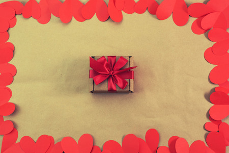 Frame of red hearts packaging with a gift. The concept of Valentines day