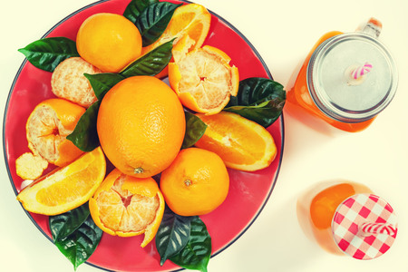 Red plate with oranges and tangerines green leaves bottle with juice on light background Top view copy space Foto de archivo