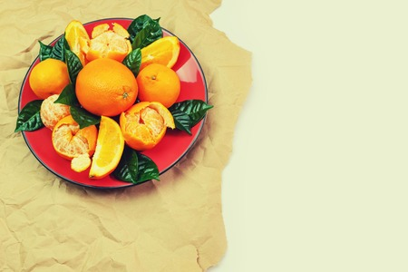 Red plate of oranges and tangerines with green leaves on a light background Top view copy space Foto de archivo