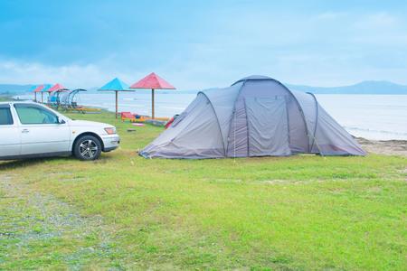 Seascape summer travel machine tent rubber boat Coastline horizon sky with clouds Stock fotó