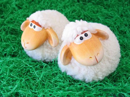 guileless: Two little toy sheeps on green grass background