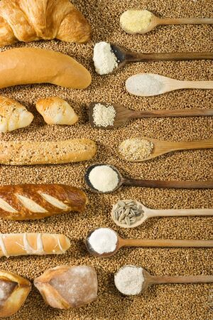Various types of bakery with wooden spoon on wheat background photo
