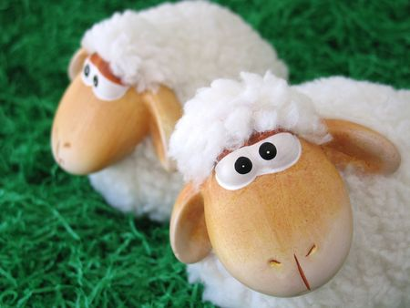 cute sheep: Two little toy sheeps on green grass background