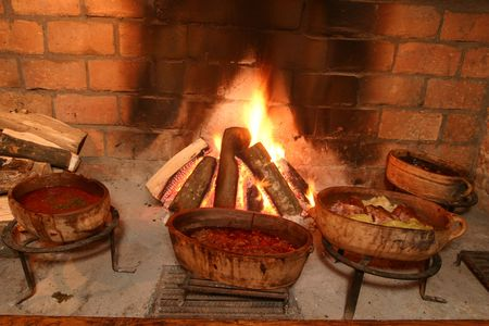 Traditional way of cooking by open fire in clay pot on tripod Stock Photo
