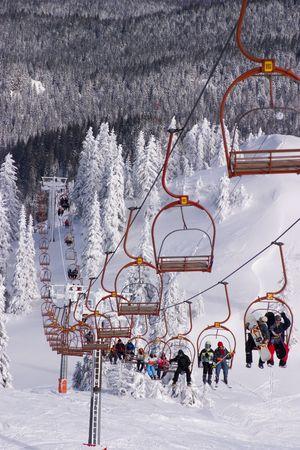 icily: Skiers riding the ski-lift on Jahorina mountain, near Sarajevo, Bosnia Stock Photo
