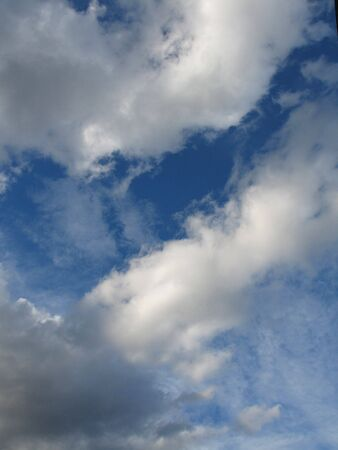 sidelight: Clouds on blue sky background with sun in sidelight Stock Photo