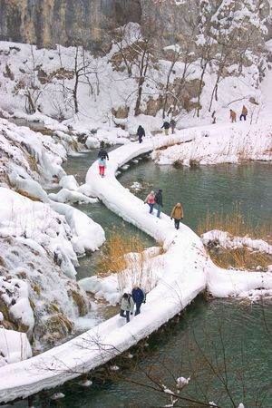 moistness: Plitvice - winter landscape with lake, path and some tourists