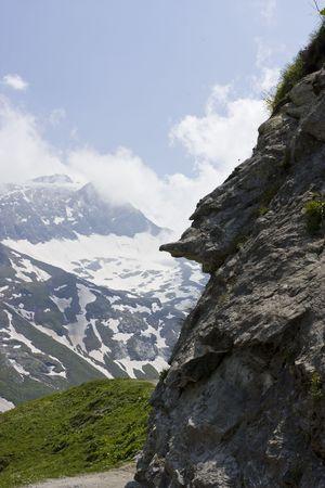 mountainside: Beautiful Austrian Alpine landscape with clouds surrounding mountain peaks Stock Photo