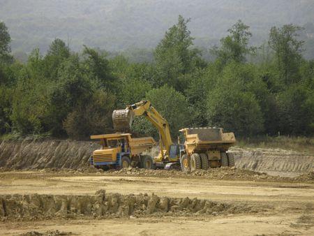 browncoal: Coal mine machines in work in field Stock Photo