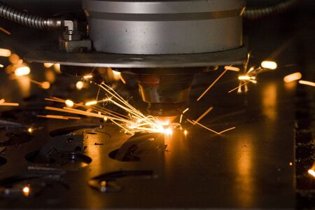 sparklet: Laser cutting metal sheet in factory, with sparks flying around
