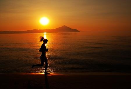 Woman running on the beach at sunset  photo