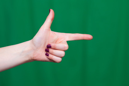 totalitarian: Hand female fingers indicates closeup on a green background