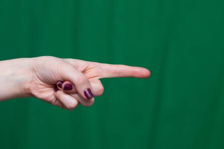 Hand female fingers indicates closeup on a green background