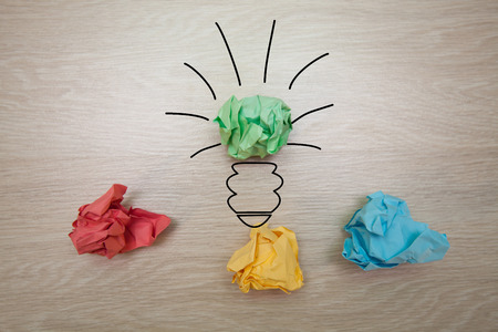 The concept, the idea of colored paper, crumpled drawn light bulb on wooden background for business presentations Stock Photo