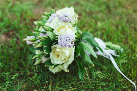 Beautiful bridal bouquet of the bride on the green grass.