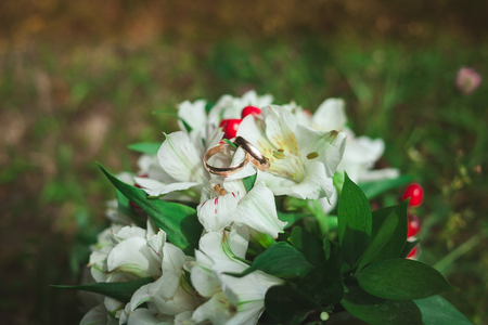 Beautiful golden wedding rings with wedding bouquet of bride on green grass in summer close-up.