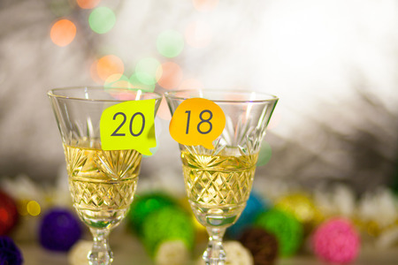 Two glasses with champagne on a table with stickers and an inscription 2018. New Years bright blurred background.
