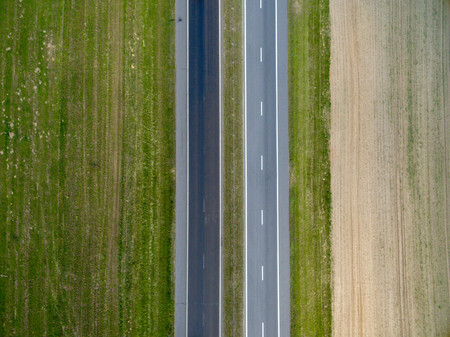Aerial top view of asphalt road through a green field in summer in Belarus. Nature from a bird's eye view Stock Photo
