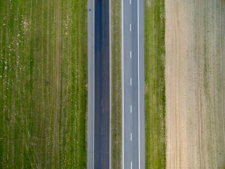 Bovenaanzicht vanuit de lucht van asfaltweg door een groen veld in de zomer in Wit-Rusland. De natuur vanuit vogelperspectief Stockfoto