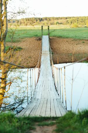 Old suspended wooden foot bridge over the river. Vertical photo on a summer day. River crossing for people