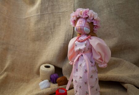 handmade motanka doll on linen fabric background Imagens