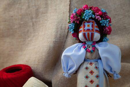 handmade motanka doll on linen fabric background