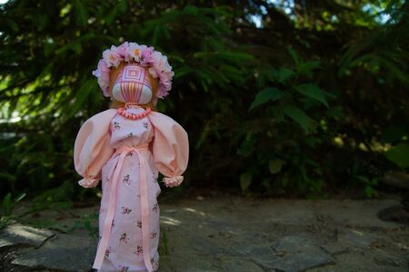 handmade motanka doll of pink color on a green background of flowers