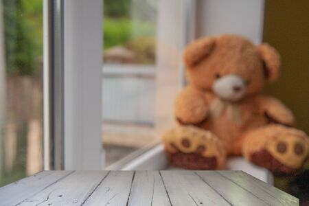 wooden table on a soft blurred toy background on a windowsill