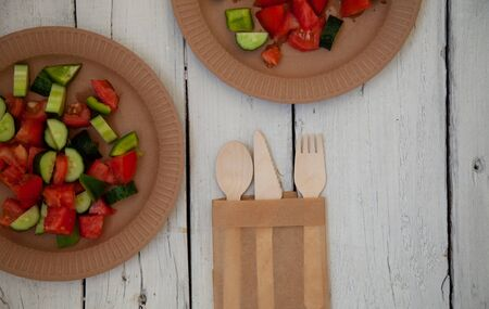 paper cardboard dishes with vegetable salad tomatoes cucumbers with wooden devices fork horse knife on a wooden table 스톡 콘텐츠
