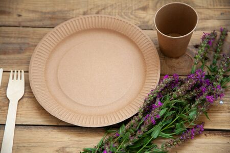 ecological disposable tableware paper cardboard empty on a wooden table with yellow flowers 스톡 콘텐츠
