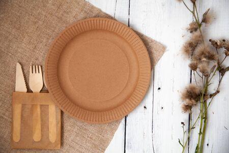 Stoviglie ecologiche usa e getta cartone di carta vuoto su un tavolo di legno bianco con fiori gialli