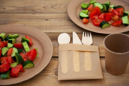 paper cardboard dishes with vegetable salad tomatoes cucumbers with wooden devices fork horse knife on a wooden table Zdjęcie Seryjne