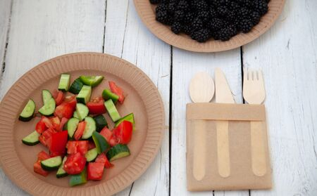 paper cardboard dishes with vegetable salad tomatoes cucumbers with wooden devices fork horse knife on a white wooden table Zdjęcie Seryjne
