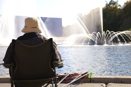 Grandfather is fishing at the fountain. large fountain. Stock Photo