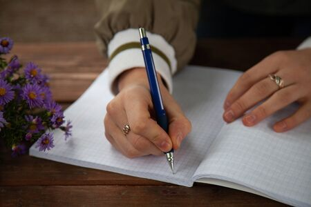 girl holding a pen in her hand. place for text.