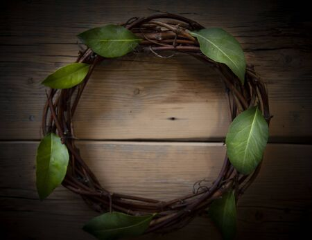 A rustic wreath made of twigs and twigs on a simple wooden background, and evergreen branches. A Christmas image with space for text, view from the top.