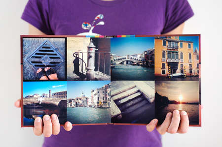 Opened square travel photo album in woman hands background