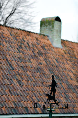 Windvane with hunter and dog opposite the traditional tile roof somewhere in Holland Stock Photo