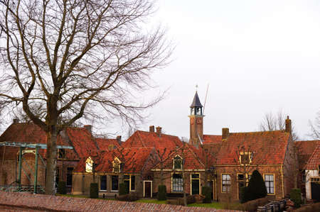 Street of old brick houses with tile roofs in Holland