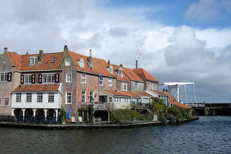 View from the bridge in Enkhuizen city in Netherlands traditional old brick buildings with tile roofs, Netherlands Editorial