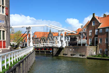 Traditional white old bridge in Enkhuizen and traditional old brick buildings with tile roofs, Netherlands