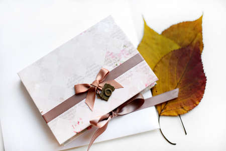 Autumn gift in craft paper and dry leaves with free copyspace